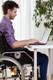 Mann auf dem Rollstuhl, der an Laptop arbeitet Lizenzfreie Stockbilder
