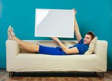 Mann auf dem Sofa, das leere Schautafel hält Lizenzfreie Stockbilder