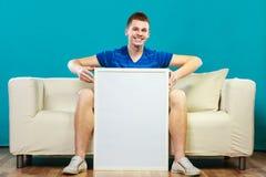 Mann auf dem Sofa, das leere Schautafel hält Stockfotos