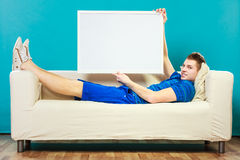 Mann auf dem Sofa, das leere Schautafel hält Stockbild