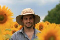 Mann auf dem Sonnenblumegebiet Stockfotos