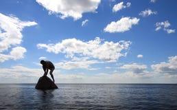 Mann auf dem Stein Stockbild