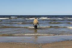 Mann auf dem Strand, der nach Gold sucht stockbild