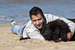 Mann auf dem Strand mit seinem Hund Stockfotos
