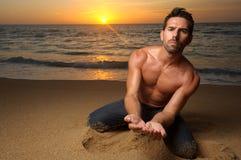 Mann auf dem Strand am Sonnenuntergang Stockbilder
