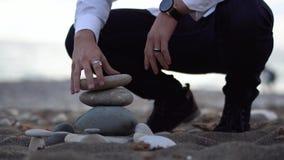 Mann auf dem Strand versuchen, eine Pyramide mit grauen Steinen zu errichten, aber seine nicht einfachen, Steine fallen unten stock video