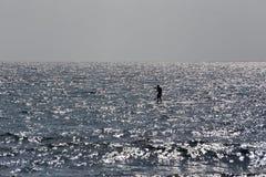 Mann auf dem Surfbrett auf dem Meer in den Sonnenuntergangsilberkrisenherden Stockbild