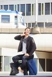 Mann auf dem TelefonAnklopfen außerhalb der Bahnstation mit Gepäck Lizenzfreie Stockfotografie