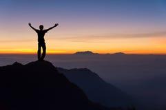 Mann auf den Berg, der zum Sonnenaufgang schaut Stockfotos