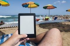 Mann auf den Strandhänden, die ebook Leser halten lizenzfreie stockbilder