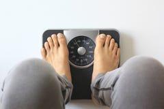 Mann auf der Gewichts-Skala für Kontrollgewicht, Diätkonzept stockfotografie
