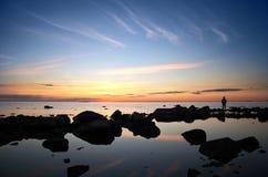 Mann auf der Küste und heller Sonnenuntergang über dem Meer Stockfotografie