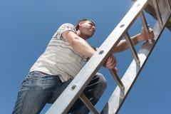 Mann auf der Leiter Stockfotos