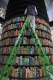 Mann auf der Leiter, die einen Turm von Regalen mit Büchern füllt stockbild