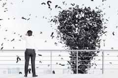 Mann auf einem Dach und einem Fragezeichentornado Stockfoto