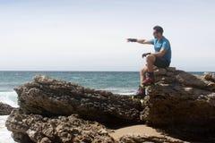 Mann auf einem Felsen am Zeigen in dem Meer Stockfotos