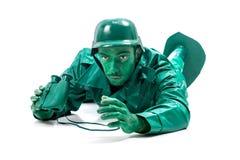 Mann auf einem grünen Spielzeugsoldatkostüm Stockfotografie