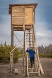 Mann auf einem hölzernen Jagdturm für Bogenschießen von wilden Tieren stockfotos