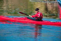 Mann auf einem roten Kajak nahe dem Ufer Kayak fahrend Stockbild