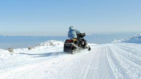 Mann auf einem Schneemobil fahrung Lizenzfreies Stockbild