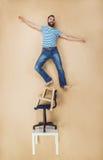 Mann auf einem Stapel von Stühlen Stockfotografie