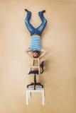 Mann auf einem Stapel von Stühlen Stockbild