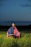 Mann auf einem Weizengebiet mit amerikanischer Flagge Stockfotos