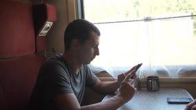 Mann auf einem Zugbahnauto hörend Musik auf dem Schreiben einer Mitteilung in einen Botesocial media Smartphone stock video footage