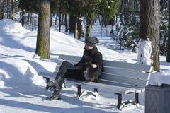 Mann auf einer Bank im Park Kalter Morgen Mannwinter Mann auf der Bank Die Sonne scheint das Gleis, Schnee, Holz Straße mit Bank  lizenzfreies stockfoto