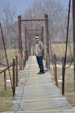 Mann auf einer Hängebrücke Stockbild