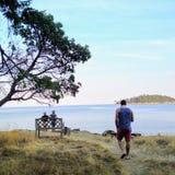 Mann auf einer Insel durch das Ufer denkend und erwägend lizenzfreie stockfotos
