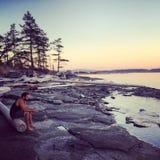 Mann auf einer Insel durch das Ufer denkend und erwägend lizenzfreie stockbilder
