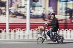 Mann auf elektrischem Fahrrad mit Anschlagtafel auf Hintergrund, Peking, China Lizenzfreie Stockfotos