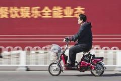 Mann auf elektrischem Fahrrad mit Anschlagtafel auf Hintergrund, Peking, China Lizenzfreies Stockfoto