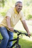 Mann auf Fahrrad draußen lächelnd lizenzfreies stockfoto