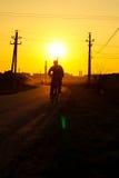 Mann auf Fahrrad geht auf die Straße während des Sonnenuntergangs Stockfotografie
