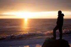 Mann auf Felsen auf dem Meer im Eis - Schattenbild Lizenzfreie Stockfotos