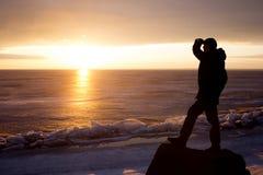 Mann auf Felsen auf dem Meer im Eis - Schattenbild Lizenzfreie Stockfotografie