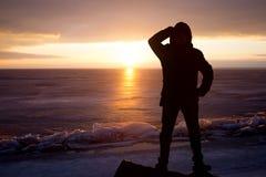 Mann auf Felsen auf dem Meer im Eis - Schattenbild Stockbilder