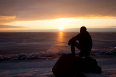 Mann auf Felsen auf dem Meer im Eis - Schattenbild Stockfotografie