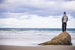 Mann auf Felsen auf sandigem Strand lizenzfreie stockbilder