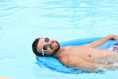 Mann auf Floss lächelnd im Swimmingpool Stockbilder