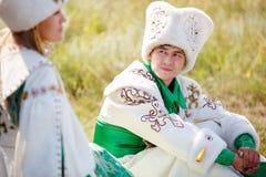 Mann auf Gras in der traditionellen Kleidung betrachtet seine geliebte Frau stockbild