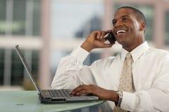 Mann auf Handy und Computer Stockbild