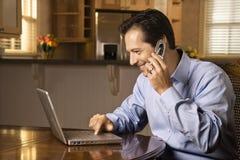 Mann auf Handy und Laptop Lizenzfreies Stockbild