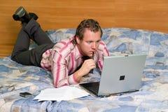 Mann auf Hotel-Bett mit Laptop lizenzfreies stockfoto