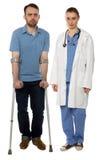 Mann auf Krücken und Dame Doktor Standing Stockfotos