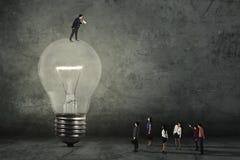 Mann auf Lampe seine Arbeitskräfte anrufend Stockbild