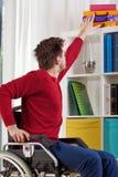 Mann auf Rollstuhl während der täglichen Aufgabe lizenzfreie stockbilder