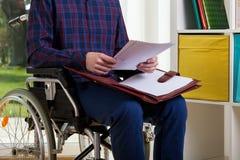 Mann auf Rollstuhllesedokumenten Stockfoto